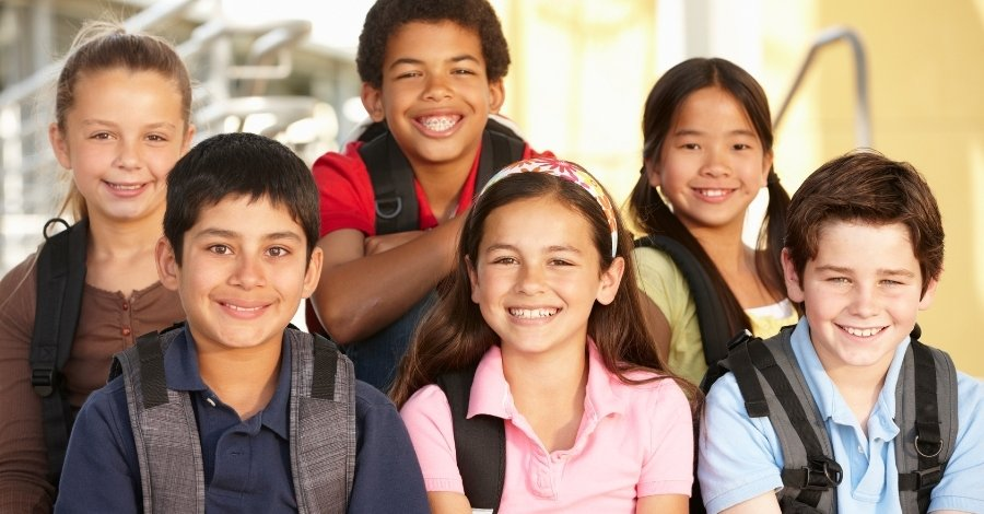 A group of tween - Middle School aged kids smiling - aguide to wht is a tween