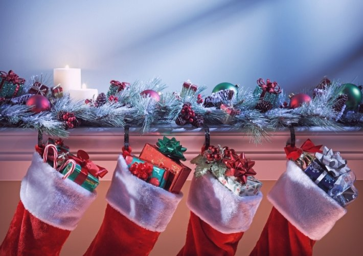 Christmas stockings stuffed with presents on a mantle piece