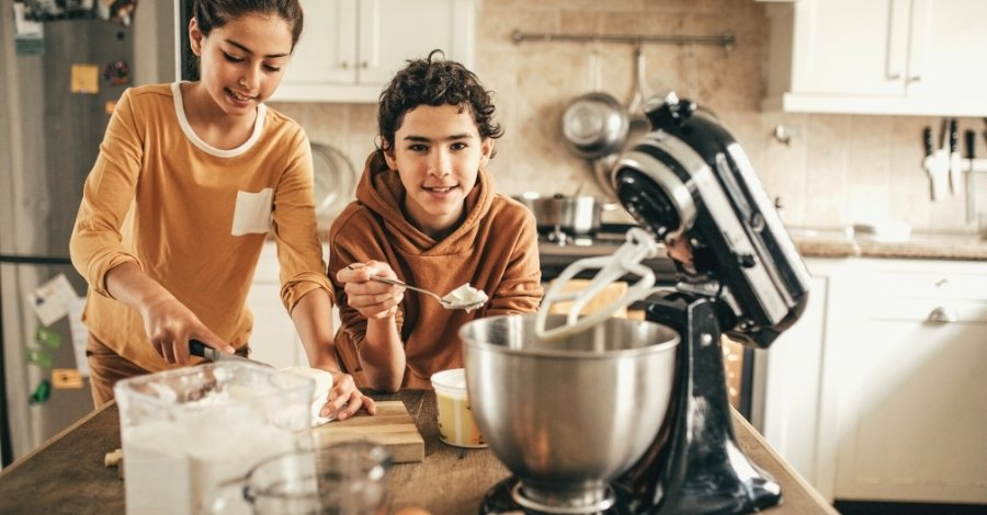 Two tweens boy and girl baking in the kitchen with a mixer