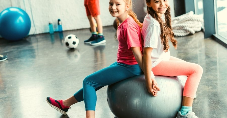 Two tween girls sitting on a gym ball - sporty girl gifts